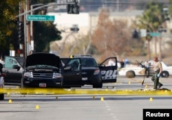 FILE - A police officer picks up a weapon from the scene of the investigation around the area of the SUV vehicle where two suspects were shot by police following a mass shooting in San Bernardino, California, Dec. 3, 2015.