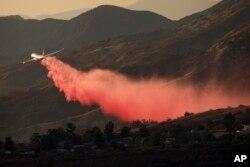 An air tanker drops retardant at a wildfire burns at a hillside in Yucaipa, Calif., Saturday, Sept. 5, 2020.