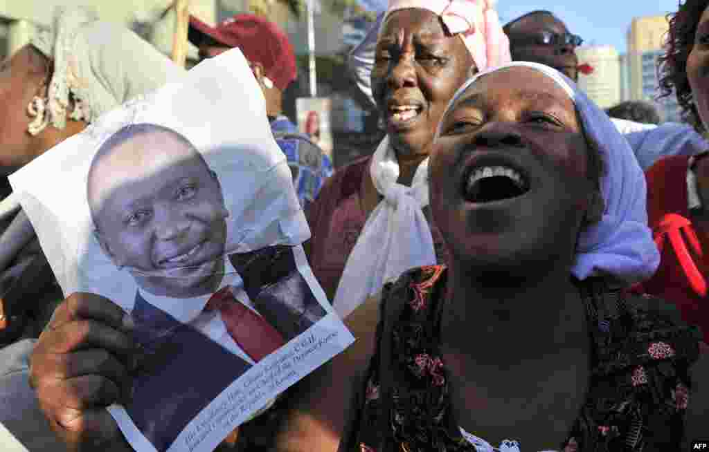Supporters of Kenya's President Uhuru Kenyatta, celebrate in the streets of Nairobi following the International Criminal Court's ruling to drop crimes against humanity charges against him, at the ICC courts at the Hague.