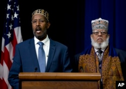 FILE - Abdisalam Adam a public school teacher and imam from St. Paul, Minn. (left) and Imam Sheikh Sa'ad Musse Roble, of the World Peace Organization in Minneapolis, participate in the White House Summit on Countering Violent Extremism, Feb. 18, 2015.