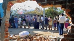 FILE - Survivors line up for aid in Armenia, El Salvador, 39 kms from the El Savadoran capital, after it was destroyed by an earthquake on January 23, 2001.
