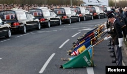 FILE - The repatriation cortege carrying the bodies of six British Army soldiers killed in Afghanistan stops at The Memorial Garden in Carterton, near Brize Norton, southern England, March 20, 2012.