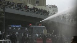 """Protesters calling themselves the """"Youth of March 24 Movement"""" demonstrate to demand for political reform and the ouster of the prime minister in front of police water canons at a main square in Amman, March 25, 2011"""