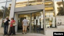 A man checks announcements outside an unemployment bureau in Athens, Greece, August 9, 2012.