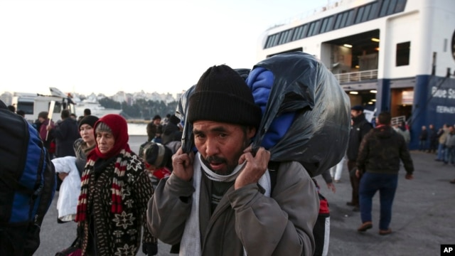 FILE - Migrants arrive at the Greek port of Piraeus, near Athens, in December. A new security report says that, since May, 43 suspected jihadists have been caught entering Europe disguised as refugees.