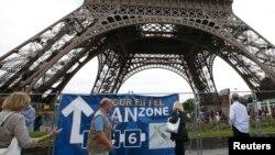 Des touristes marchent autour de la Tour Eiffel, à Paris, France, le 28 juin 2016.