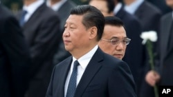 FILE - Chinese Premier Li Keqiang, right, walks past Chinese President Xi Jinping as they arrive to the Monument to the People's Heroes during a ceremony marking Martyr's Day at Tiananmen Square in Beijing, Sept. 30, 2014.