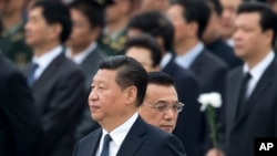 FILE - Chinese President Xi Jinping arrives at the Monument to the People's Heroes during a ceremony marking Martyr's Day at Tiananmen Square in Beijing, China, Sept. 30, 2014. (AP Photo/Andy Wong)
