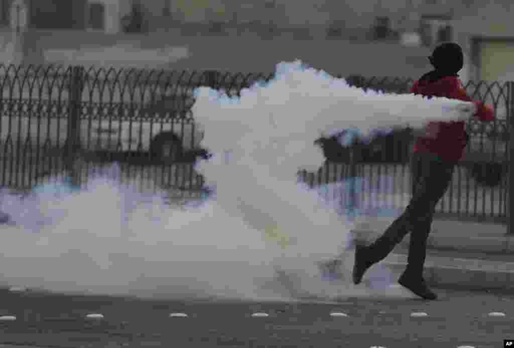 A Bahraini anti-government protester throws back a tear gas canister fired by riot police during clashes in Karzakan village, Bahrain, Thursday, Dec. 11, 2014. Clashes erupted after the funeral for an elderly man killed in an explosion Tuesday. (AP Photo/