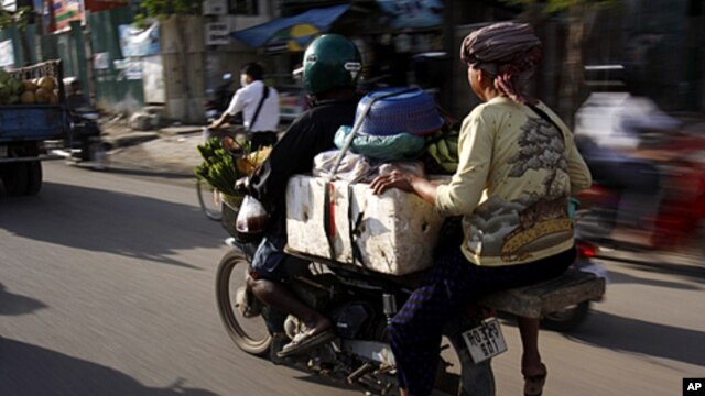 A motorcycle taxi driver carries a Cambodian vendor on his motorcycle to a market in Phnom Penh, Cambodia, July 23, 2011.