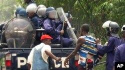 Un homme arrêté par la police congolaise qui le tire par les habits.