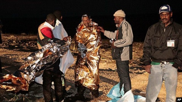 Migrants receive assistance as they arrive on the tiny island of Lampedusa, Italy, early Sunday, May 8, 2011