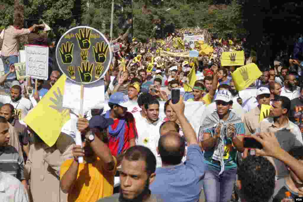 Protesters hold up four fingers as they march in Maadi, southern Cairo, Sept. 20, 2013. (Hamada Elrasam for VOA)