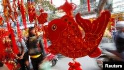 Những đồ trang trí trong dịp Tết được bày bán trên đường phố Hà Nội. Người Việt đứng thứ 2 trên thế giới về tiết kiệm tiền nhưng một chuyên gia cho rằng họ phung phí quá nhiều cho dịp Tết cổ truyền.