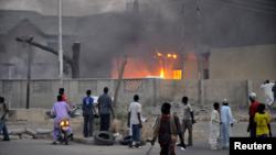 Warga menyaksikan kebakaran di kantor polisi akibat bom di kota Kano, Nigeria. (Foto: Dok)