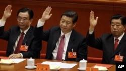 2012年11月14日资料照片:当时的中国国家副主席习近平(中)中央纪委贺国强(左)和中国人民政治协商会议主席贾庆林(右)在在北京人民大会堂举手批准工作报告