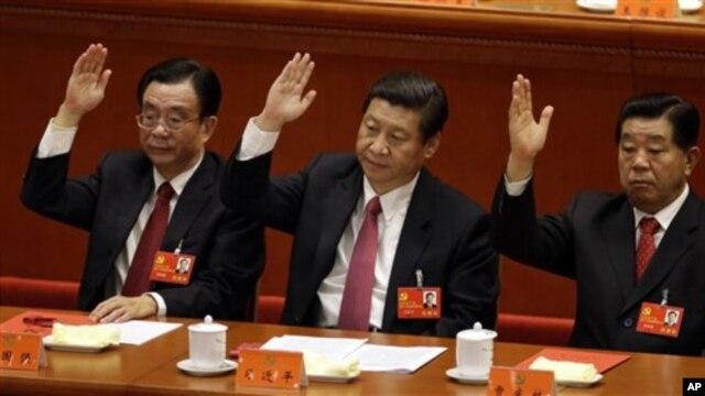 14일 중국 공산당 제18차 전국대표대회에서 거수로 업무보고를 승인하는 시진핑 부주석 (가운데), 허궈창 공산당 중앙조직부 부장 (왼쪽), 자칭린 전국인민정치협상회의 주석.