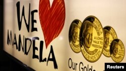 A banner advertises gold coins with the image of former South African President Nelson Mandela, Johannesburg, December 9, 2012.