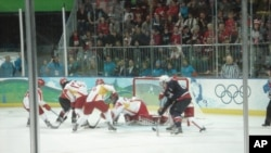 China's Goalie dives to make a save against the US team in Olympic Women's hockey in Vancouver