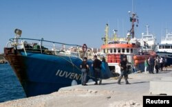 Italian police stand around the German NGO Jugend Rettet ship Iuventa in Lampedusa harbor, Italy, Aug. 2, 2017.