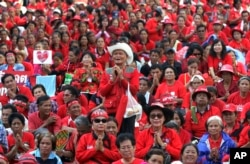 """FILE - In this May 19, 2012, file photo, """"red shirts"""" protesters attend a prayer session during a rally at Ratchaprasong Intersection in Bangkok, Thailand. The Red Shirts rose in response after Thaksin was ousted in a September 2006 military coup. (AP)"""