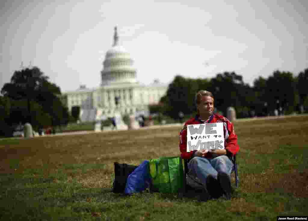 """Um funcionário do governo que foi despedido temporariamente senta-se sozinho na esplanada de Washington com ur cartaz que diz """"Queremos trabalhar"""""""