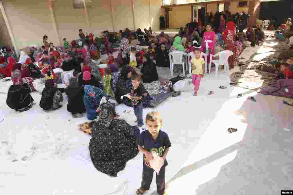 Iraqi Shi'ite Turkmen families fleeing the violence in Tal Afar arrive in Shangal, a town in Nineveh province, Iraq, June 17, 2014.