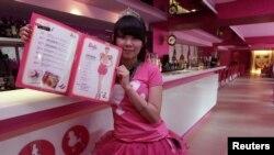 Seorang pelayan di kafe bertema Barbie berpose dengan buku menu. (Reuters/Pichi Chuang)