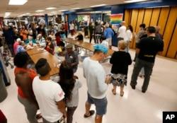 Personas en un refugio de la Cruz Roja en una escuela secundaria del Norte de Miami Beach hace fila para almorzar. Sept. 8, 2017.