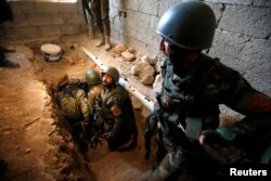 FILE - Peshmerga forces inspect a tunnel used by Islamic State militants in the town of Bashiqa, after it was recaptured from the Islamic State, east of Mosul, Iraq, Nov. 12, 2016.