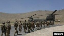 Tentara NATO berbaris memasuki helikopter Chinook menyusul upacara serah terima keamanan di akademi militer di luar Kabul (18/6).