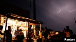 FILE - People gather at a local shop during a thunderstorm in the outskirts of Dhaka, Banglaesh. The South Asian country has seen a near-record number of deaths in 2016 from a phenomenon that appears to be worsening with climate change: lightning strikes.