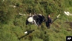 En esta imagen de video provista por NBC10 Philadelphia, un rescatistas examina el helicóptero en Lumberton, New Jersey, donde murió Troy Gentry.