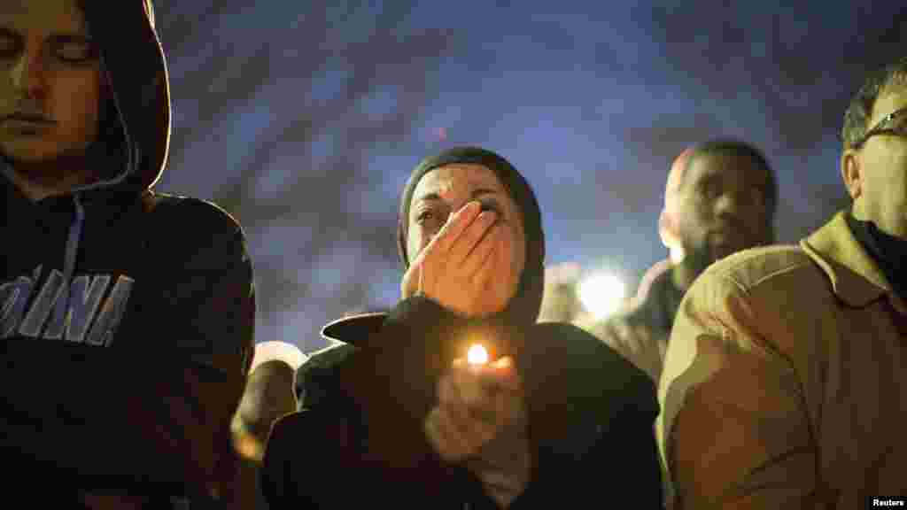 A woman cries as a video is played during a vigil on the campus of the University of North Carolina for three young Muslims slain in Chapel Hill, N.C., Feb. 11, 2015.