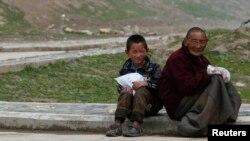지난 5월 티베트 장탐 조낭 사원 근처 길거리에서 한 티베트 소년과 남성이 앉아있다.(자료사진) 휴먼라이츠워치는 중국 정부가 2006년 이후 티베트인 2백만명을 강제로 이주시켰다고 밝혔다.