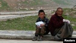 Người đàn ông và một cậu bé Tây Tạng ngồi gần Tu viện Jonang Dzamthang. Trung Quốc nhấn mạnh rằng các vụ dời cư là hoàn toàn trên căn bản tự nguyện và người dân Tây Tạng biết ơn vì có được nhà mới.