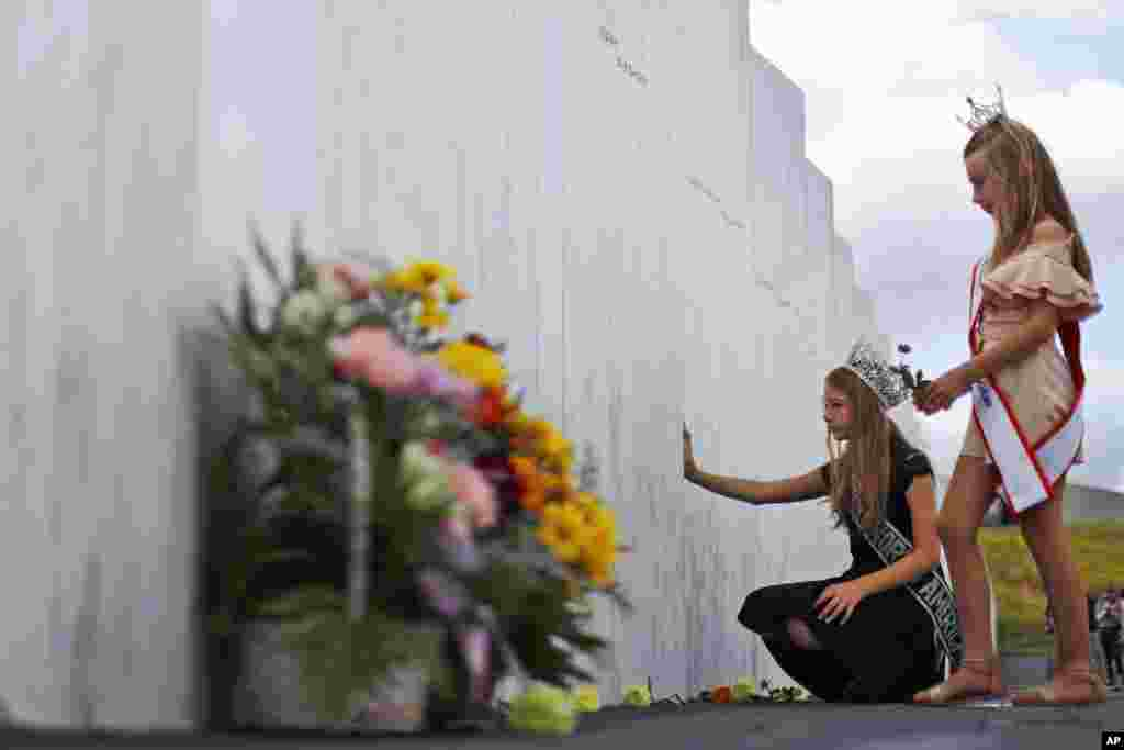 Mackenzie, right, and Madison Miller from Avonmore, Pa., visit the Wall of Names at the Flight 93 National Memorial in Shanksville, Pa., Thursday, Sept. 10, 2020, as the nation prepares to mark the 19th anniversary of the Sept. 11, 2001, attacks. The Wall of Names honors the 40 people killed in the crash of Flight 93. (AP Photo/Gene J. Puskar)
