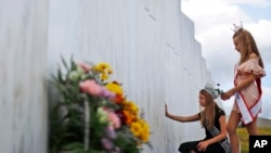 Mackenzie, right, and Madison Miller from Avonmore, Pa., visit the Wall of Names at the Flight 93 National Memorial in Shanksville, Pa., Thursday, Sept. 10, 2020, as the nation prepares to mark the 19th anniversary of the Sept. 11, 2001, attacks. The Wall