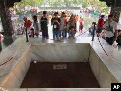 Para pengunjung melihat lubang sumur tempat jenazah enam jenderal dan satu perwira muda Angkatan Darat dikubur dalam peristiwa G30S 1965, di Monumen Pancasila Sakti, Jakarta, 15 Oktober 2017. (Foto: AP)