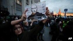"""Một phụ nữ giương tấm ảnh của Tông thống Nga Vladimir Putin. với hàng chữ """"Có nên để kẻ trộm cắp ở trong điện Kremlin? trong một cuộc biểu tình ở Moscow, Nga, ngày 21/4/2021 để ủng hộ ông Alexei Navalny, nhà bất đồng đang bị cầm tù. REUTERS/Maxim Shemetov"""