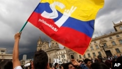 FILE - A supporter of the peace deal between the Colombian government and rebels of the Revolutionary Armed Forces of Colombia waves a flag during a rally in front of Congress, in Bogota, Colombia, Oct. 3, 2016. After Colombians rejected the deal, both sides are returning to talks in Cuba.