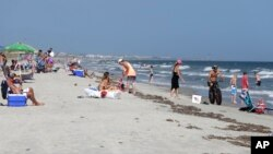 FILE - Vacationers relax on the beach and in the surf at Oak Island, N.C. — an area where two shark attacks have occurred in the last two weeks.