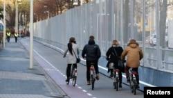 Gedung pertemuan G-7 dan Uni Eropa di Den Haag, Belanda dikelilingi dengan pagar pengaman sementara warga bersepeda (23/1).