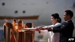 Peraih medali emas Olimpiade tiga kali Jepang Saori Yoshida (kiri) dan Tadahiro Nomura (kanan) menyalakan api Olimpiade Tokyo 2020 dengan obori Olimpiade yang dibawa dari Yunani, di Pangkalan Angkatan Udara Matsushima di Higashimatsushima, Jepang, 20 Maret 2020.