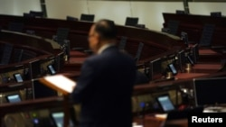 FILE - Empty seats of pro-democracy legislators are seen in the background during debate on an electoral reform bill at the Legislative Council in Hong Kong, May 26, 2021.