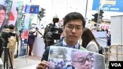 區諾軒展示疑似建制派支持者衝突的照片 (美國之音特約記者 湯惠芸拍攝 )