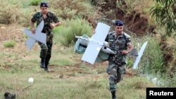Chiến binh quân đội Libăng mang theo các mảnh vỡ của một máy bay không người lái của Israel bị rơi tại vùng nông thôn Marjeyoun, phía nam Libăng ngày 20/9/2014.