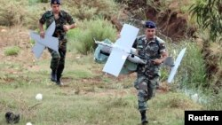 Lebanese soldiers carry parts of an Israeli MK drone that fell in South Lebanon's Marjeyoun countryside near the border with Israel. Israeli media said the IDF confirmed the drone was from Israel.