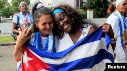 쿠바 정부가 미국과 약속 이행으로 석방한 반체제 인사 53중 2명이 11일 하바나에서 국기를 들고 기뻐하고 있다.