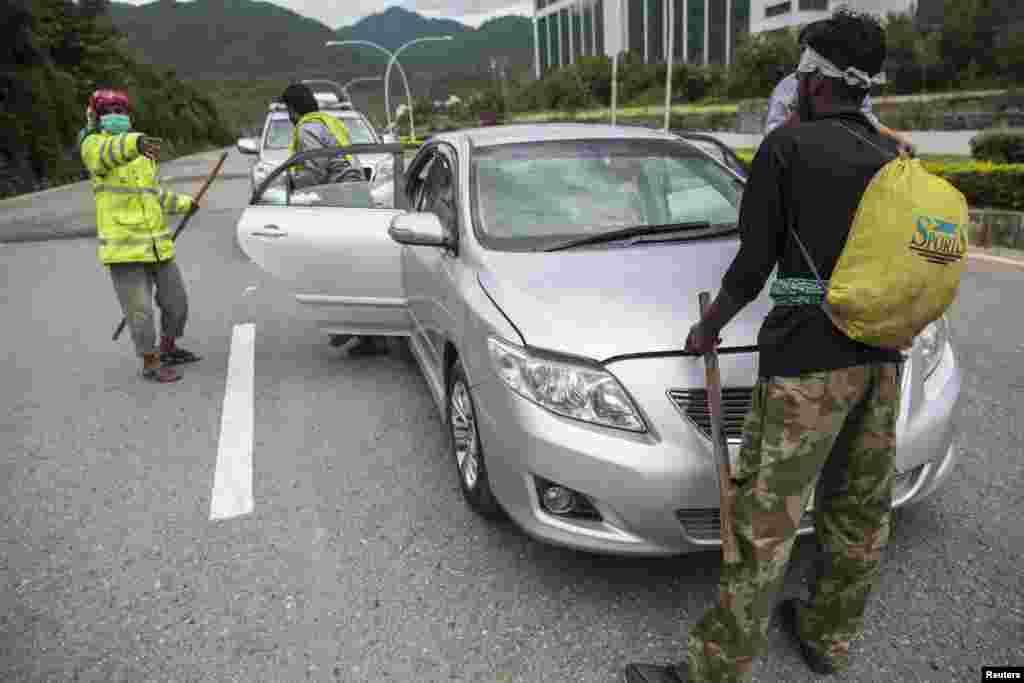 احتجاج کرنے والے گاڑیوں کو ایک مقام سے آگے بڑھنے سے قبل اُن کی تلاشی لیتے ہیں۔